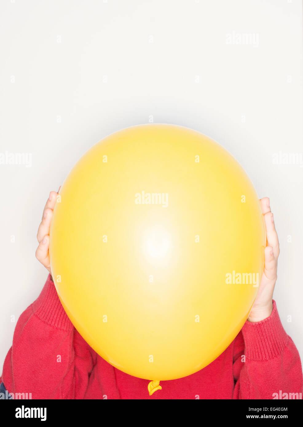 Explotación infantil globo amarillo delante de la cara. Momento en el estilo de vida de diversión. Imagen De Stock