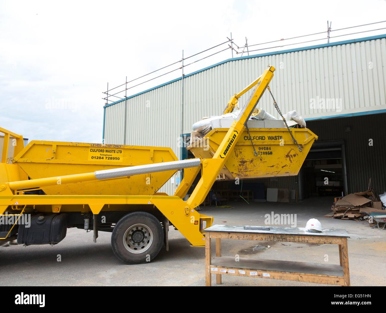 Un salto / contenedor siendo cargados en un camión en el REINO UNIDO Imagen De Stock
