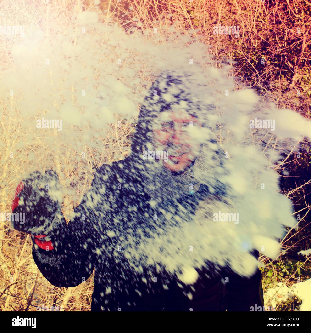 Un hombre joven lanzando una bola de nieve al observador Imagen De Stock