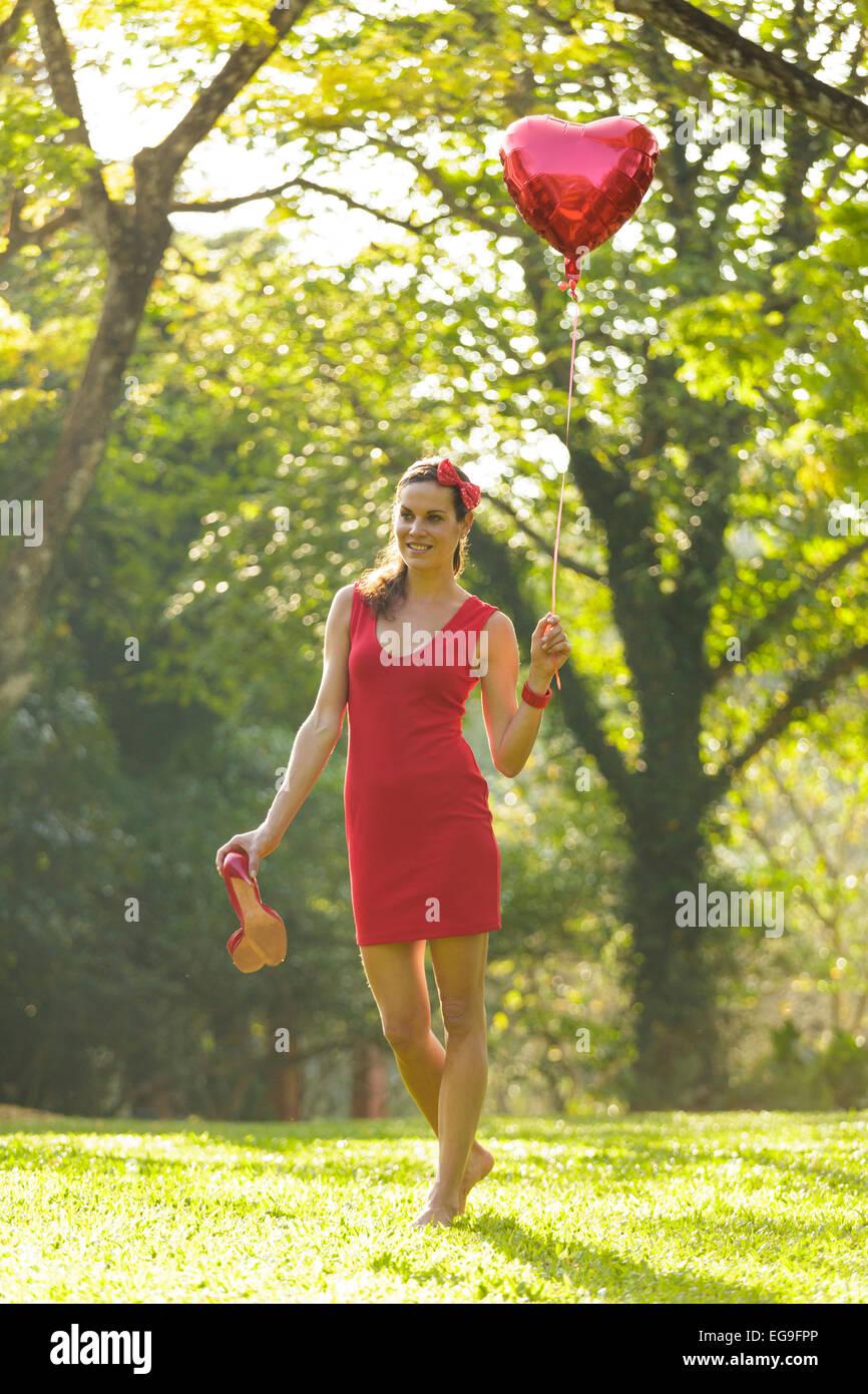 Mujer con globos con forma de corazón rojo caminando en el parque Imagen De Stock
