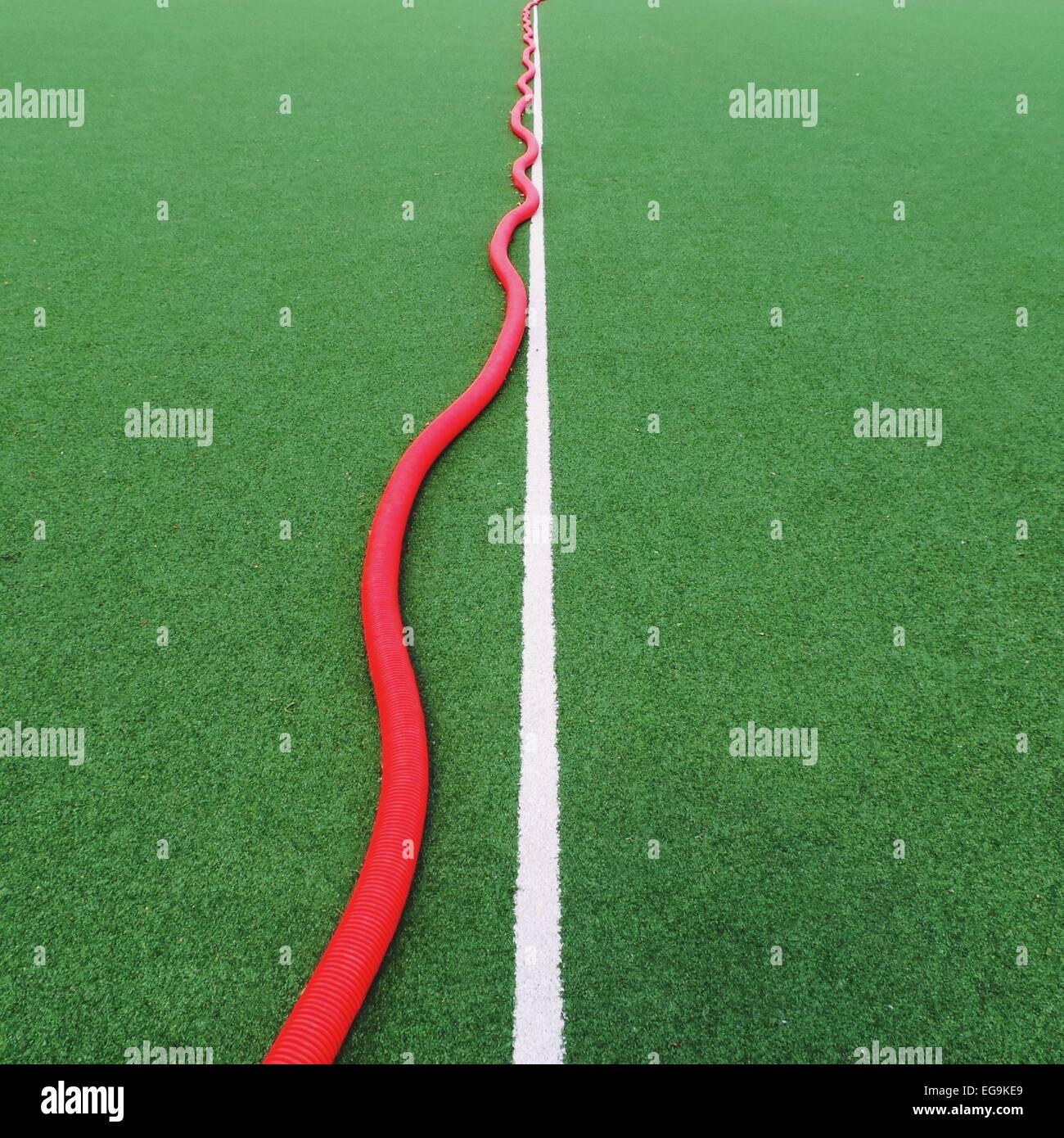 Sola línea blanca sobre el verde campo de deportes, y el tubo rojo Imagen De Stock