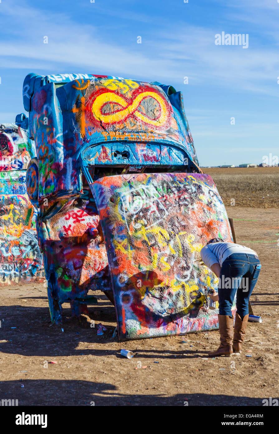 Mujer joven de pintura a un coche en el Cadillac Ranch, una instalación de arte público justo en las afueras Imagen De Stock