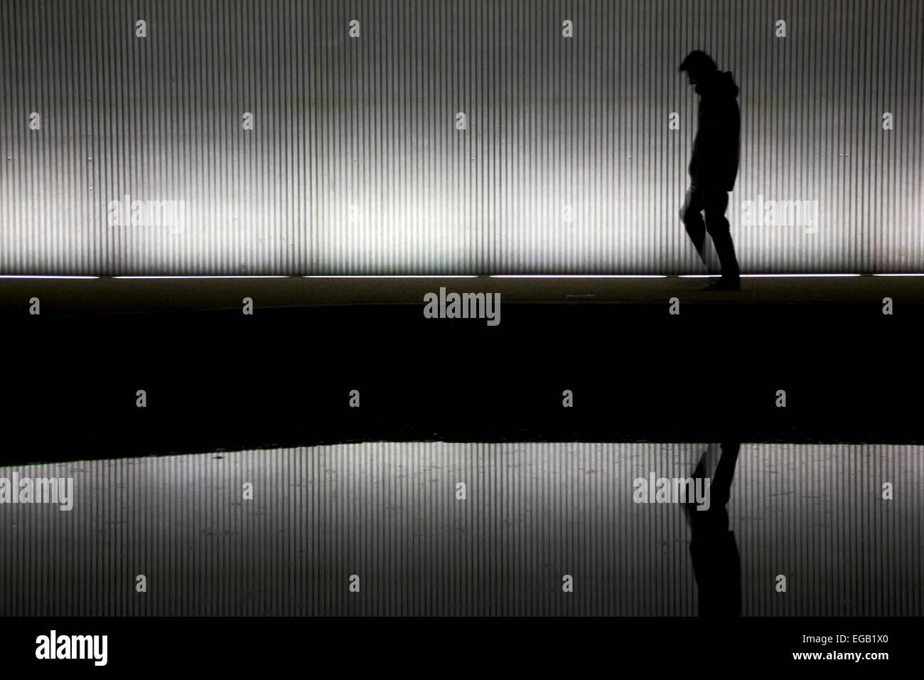 Hombre solitario caminando debajo de un puente/túnel Foto de stock