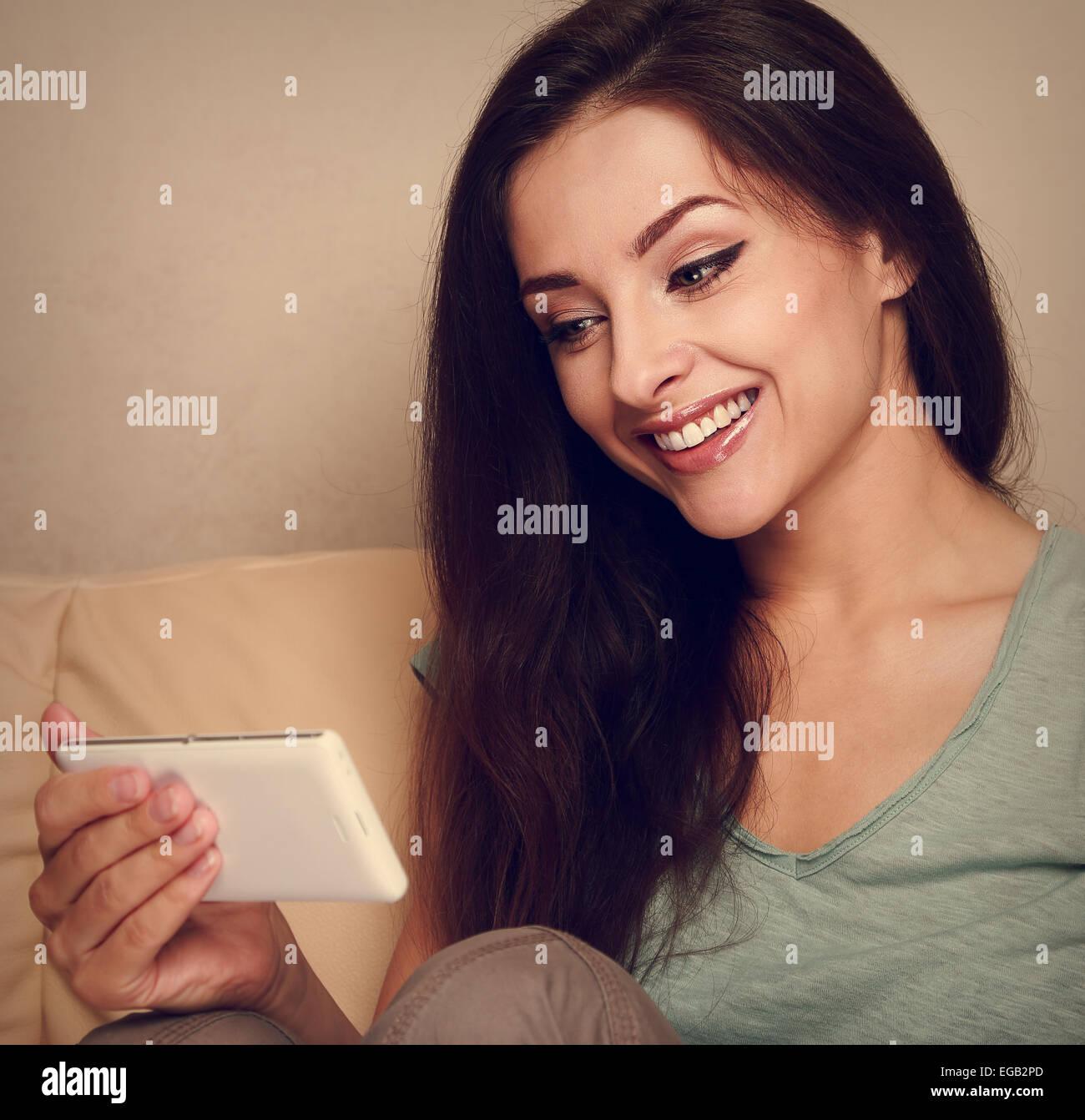 Hermosa mujer mirando en el teléfono móvil y sonriente. Retrato Vintage Foto de stock