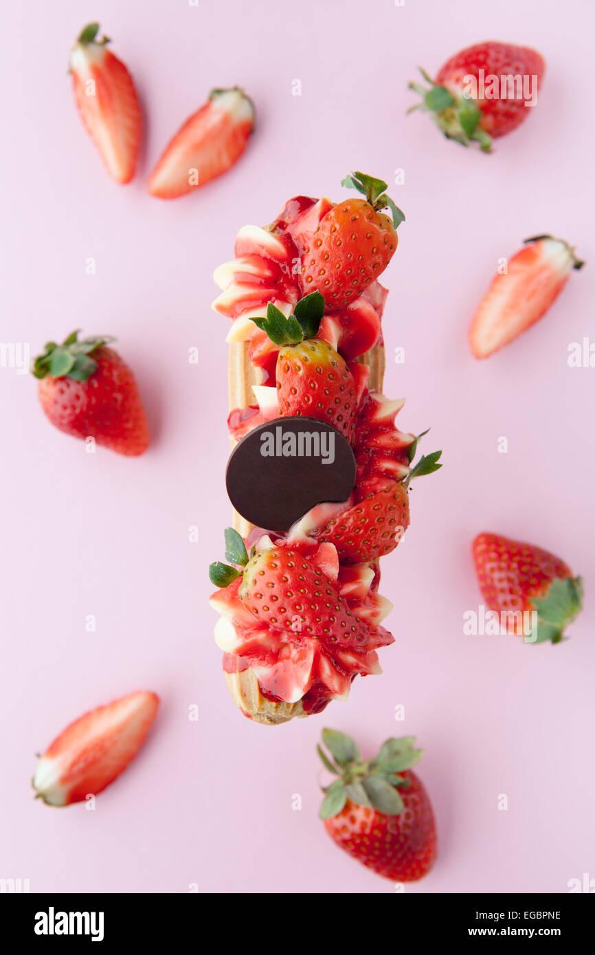 Exquisito postre cremoso eclair con fresas frescas Imagen De Stock