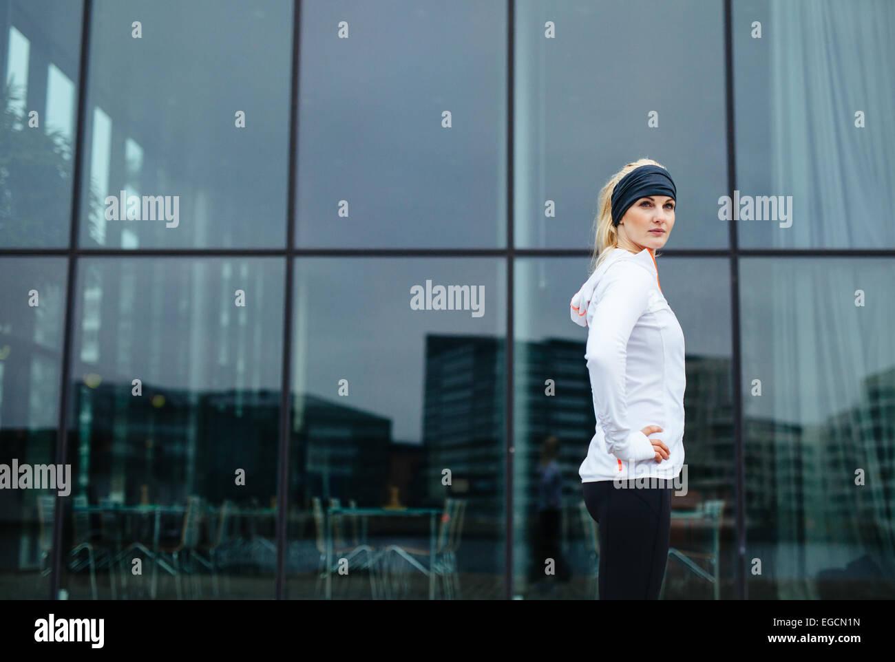 Retrato de seguros joven de pie con las manos en las caderas mirando a la cámara. Modelo de Fitness al aire Imagen De Stock