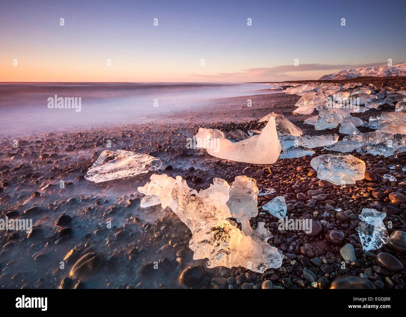 Roto el hielo de los icebergs se lavan en la playa al amanecer negro Jokulsarlon Jokulsarlon sudeste de Islandia Imagen De Stock