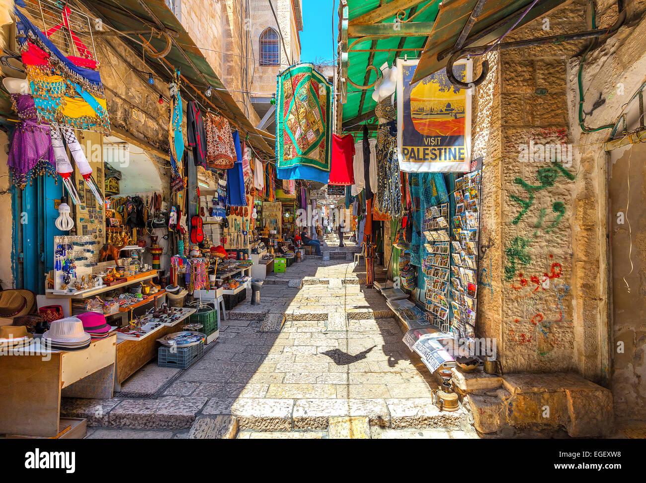 Estrechas calles de piedra de sillería con recuerdos típicos y mercancías en bazar en Jerusalén. Imagen De Stock