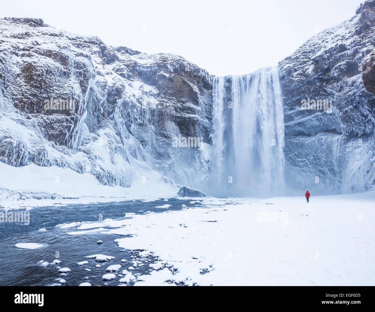 Un hombre de chaqueta roja a Catarata Skogafoss en invierno Skogar sur de Islandia Islandia Europa Imagen De Stock