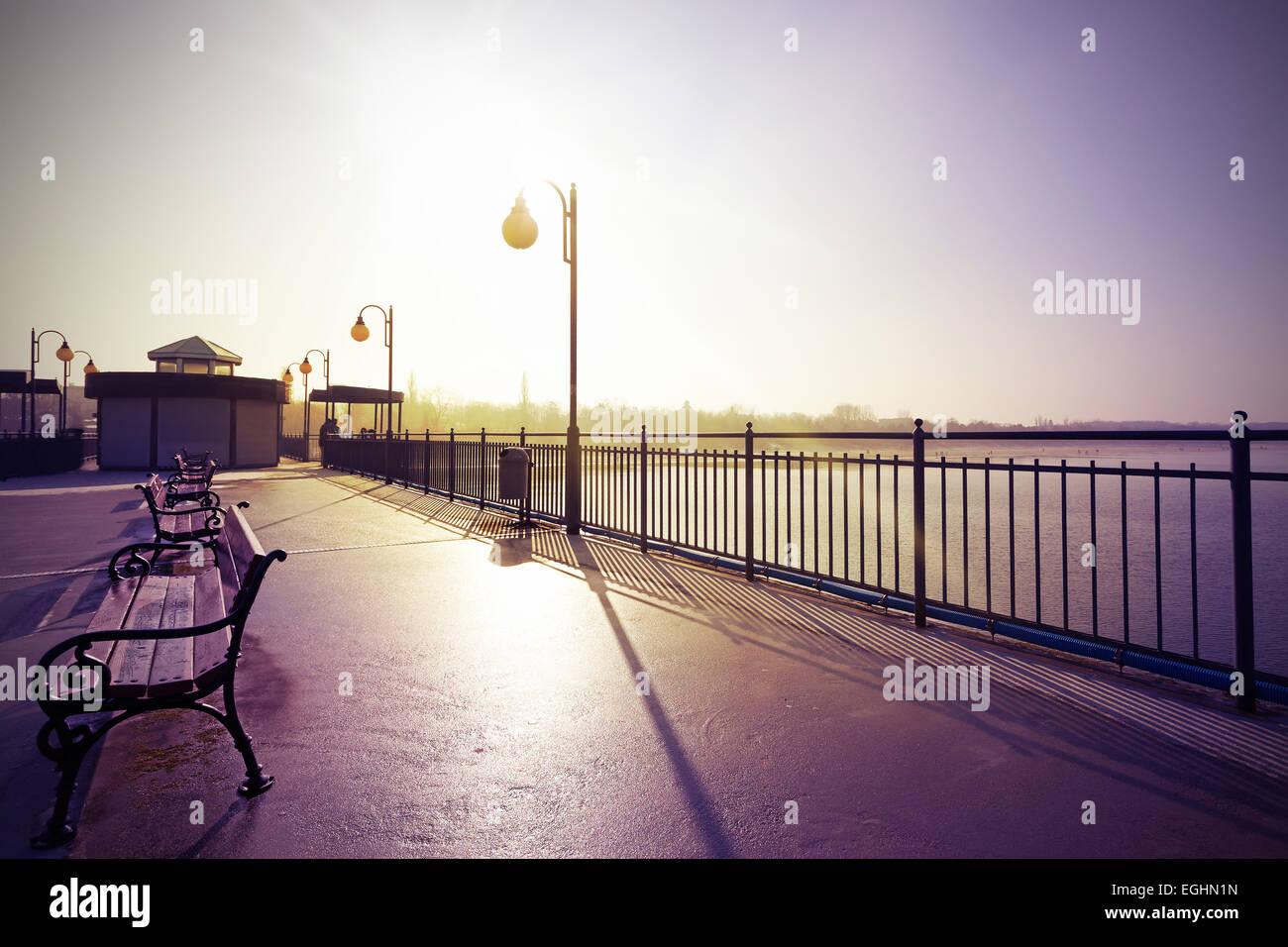 Vintage Retro nostálgico filtrada imagen del paseo marítimo contra el sol. Imagen De Stock