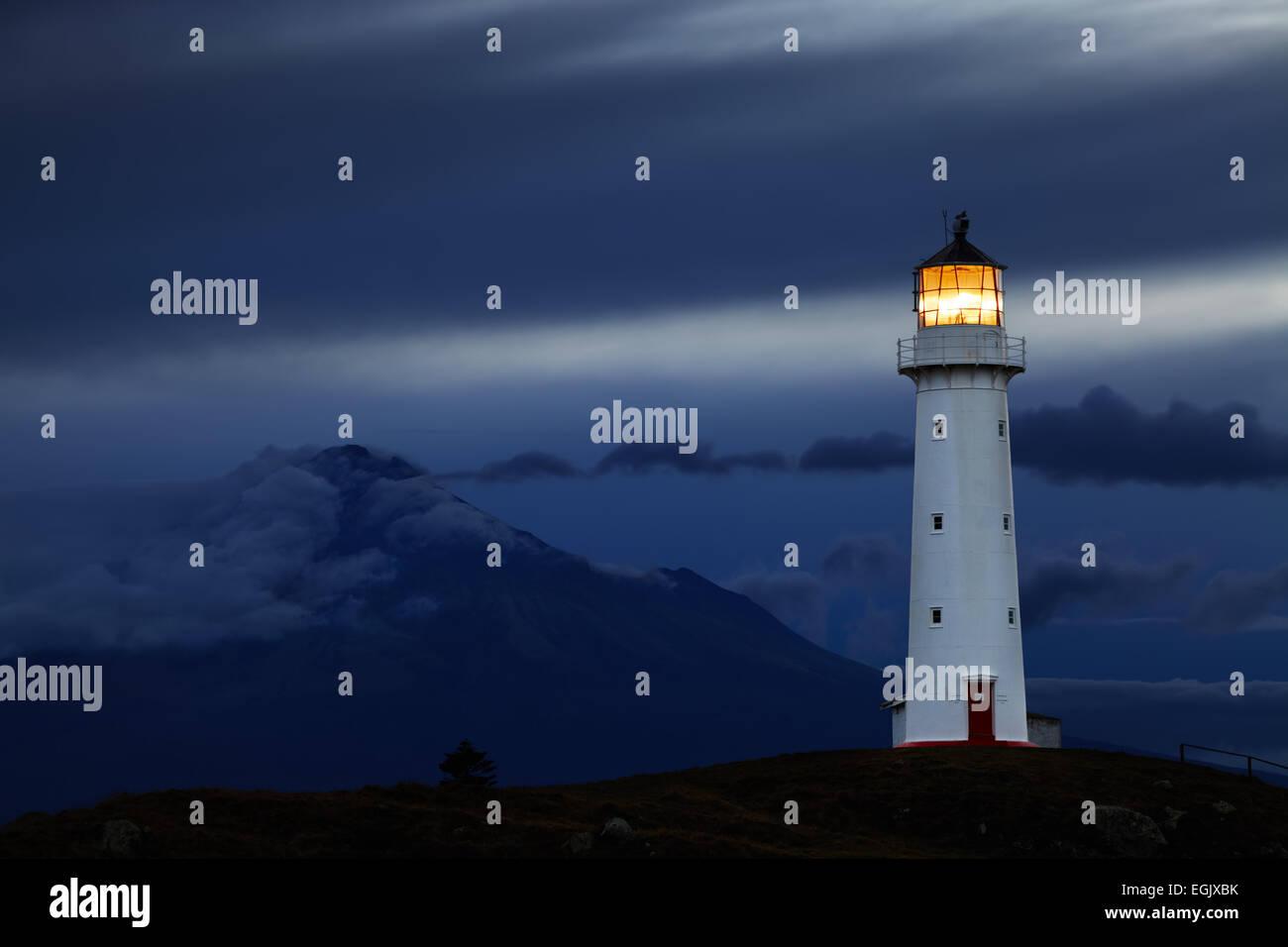 Faro de Cabo Egmont y monte Taranaki sobre antecedentes, Nueva Zelanda Imagen De Stock