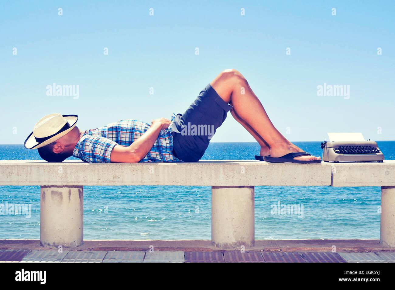 Una vieja máquina con una página en blanco y un joven acostado en un banco cerca de la calle del mar, Imagen De Stock