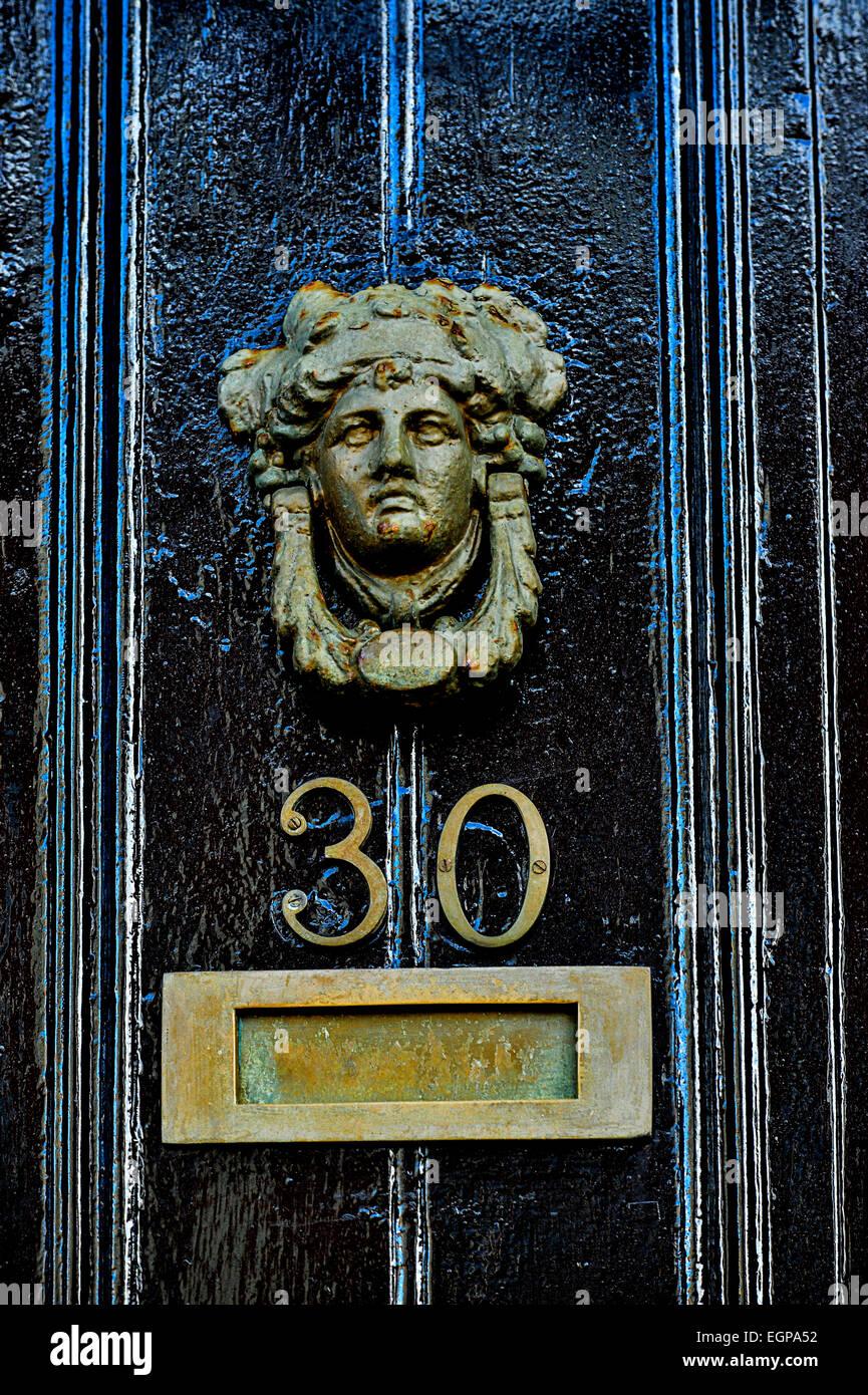 Puerta de latón de estilo georgiano martinete representando cabeza humana con letter box en puerta pintadas Imagen De Stock