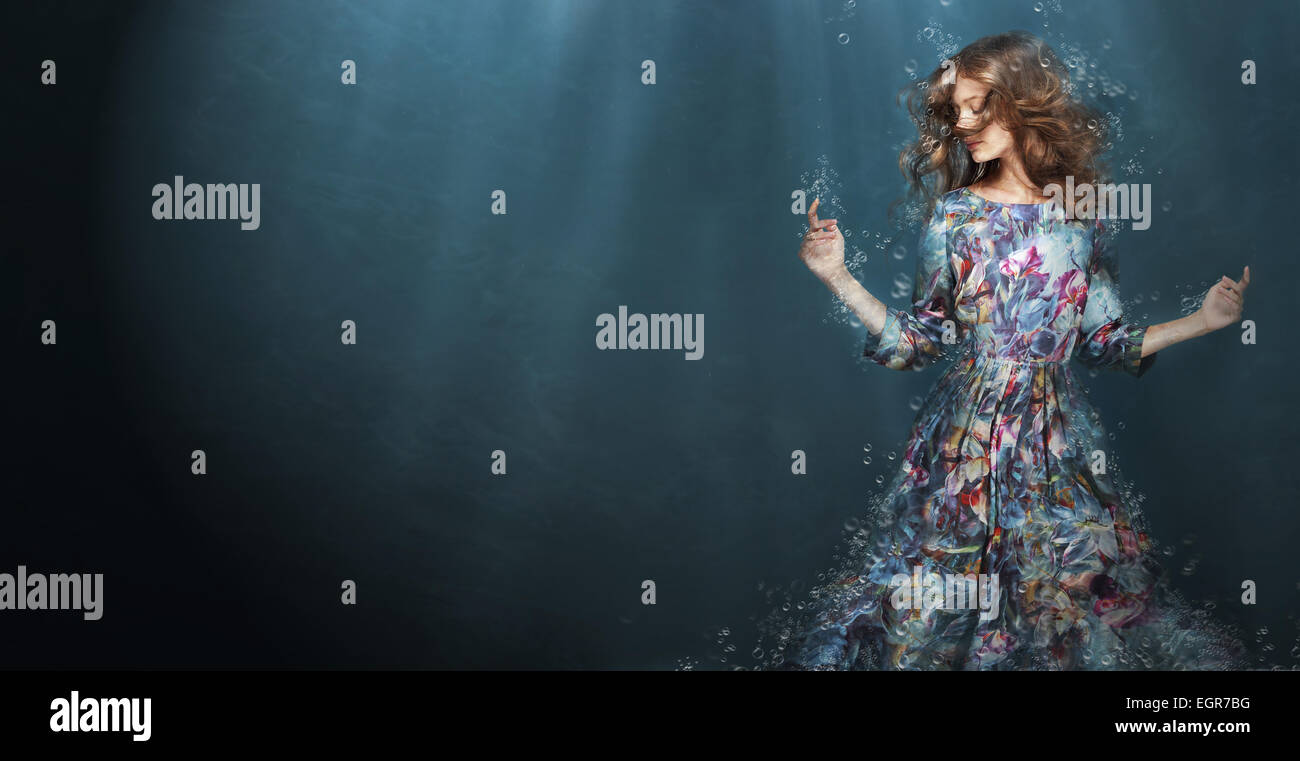 La inmersión. Mujer en el azul profundo del mar. Fantasy Foto de stock