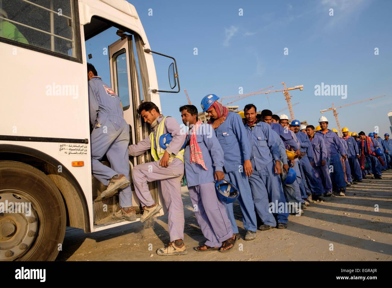 Los trabajadores de la construcción en colas para llegar en autobús a cuartos vivos al final de la jornada Imagen De Stock