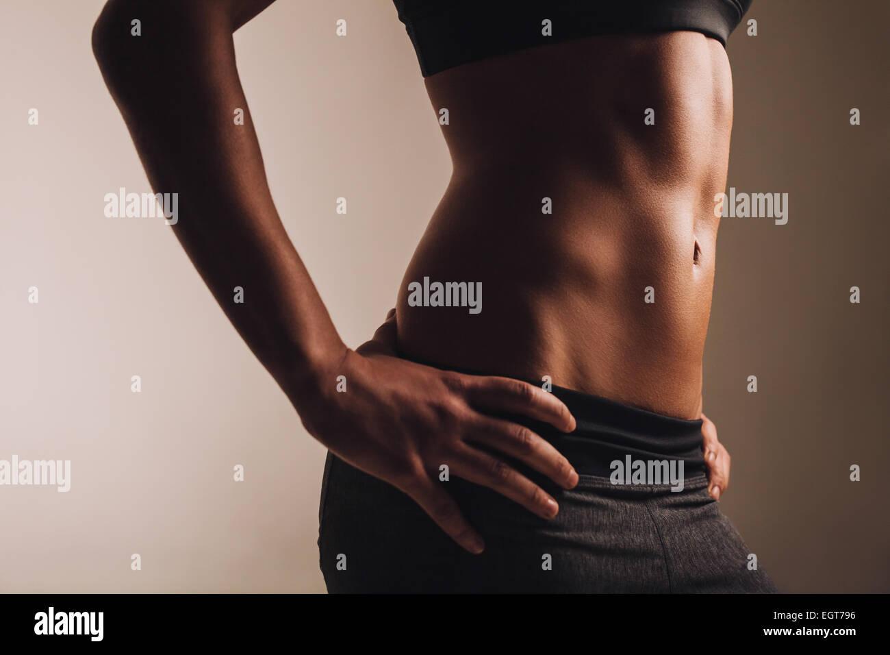Primer plano de la joven con la cintura muscular de los músculos abdominales. Abs de colocar la atleta femenina. Foto de stock