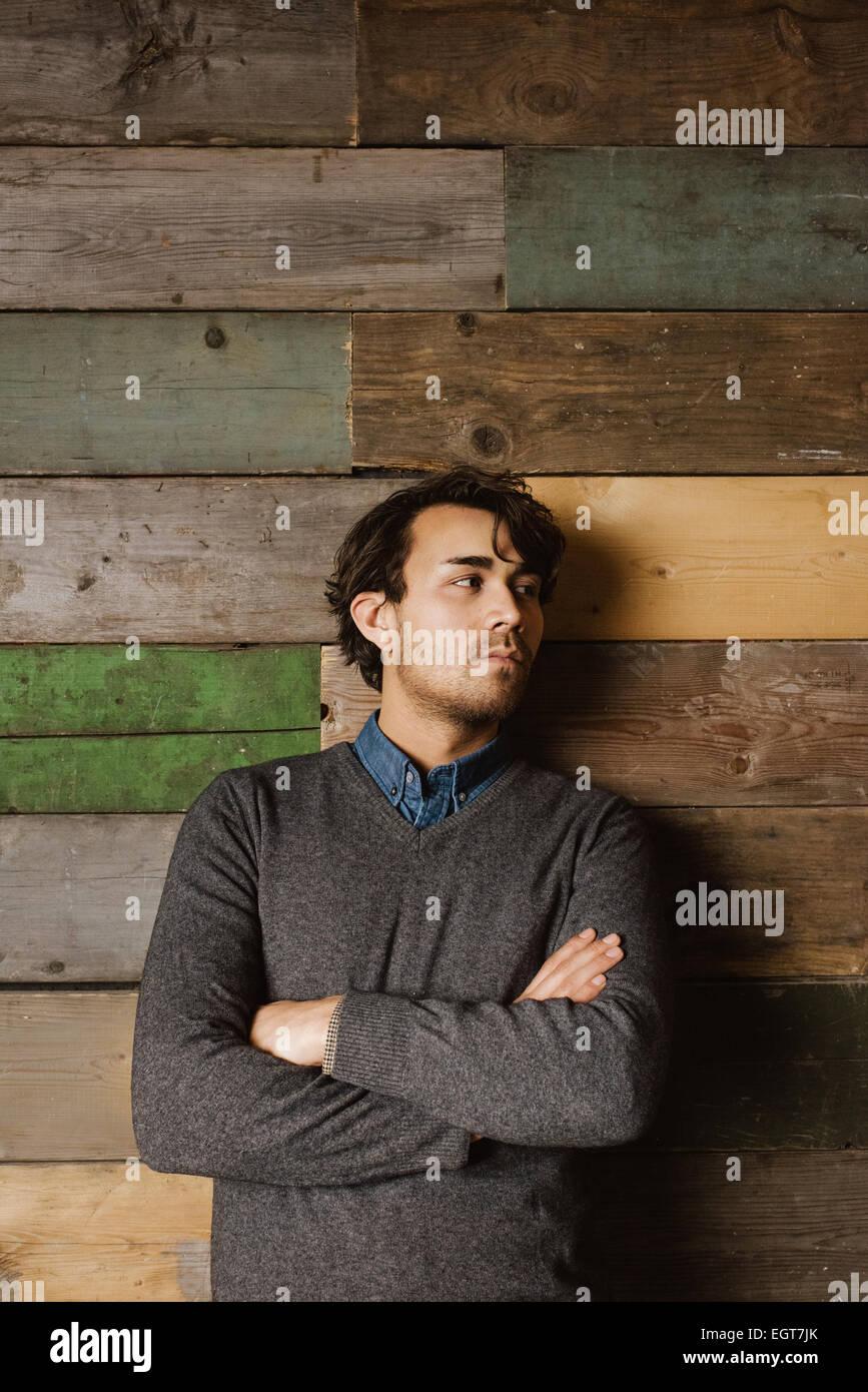 Apuesto joven hombre de negocios apoyado contra una pared de madera con sus brazos cruzados mirando a otro lado. Foto de stock