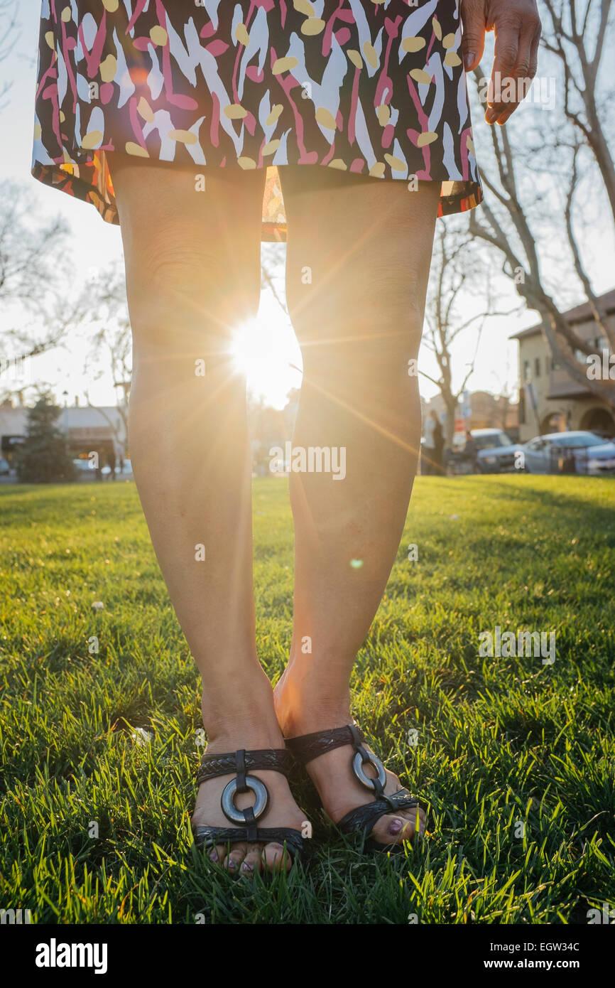 Las piernas de una mujer con el sol brillando entre ellos. Foto de stock