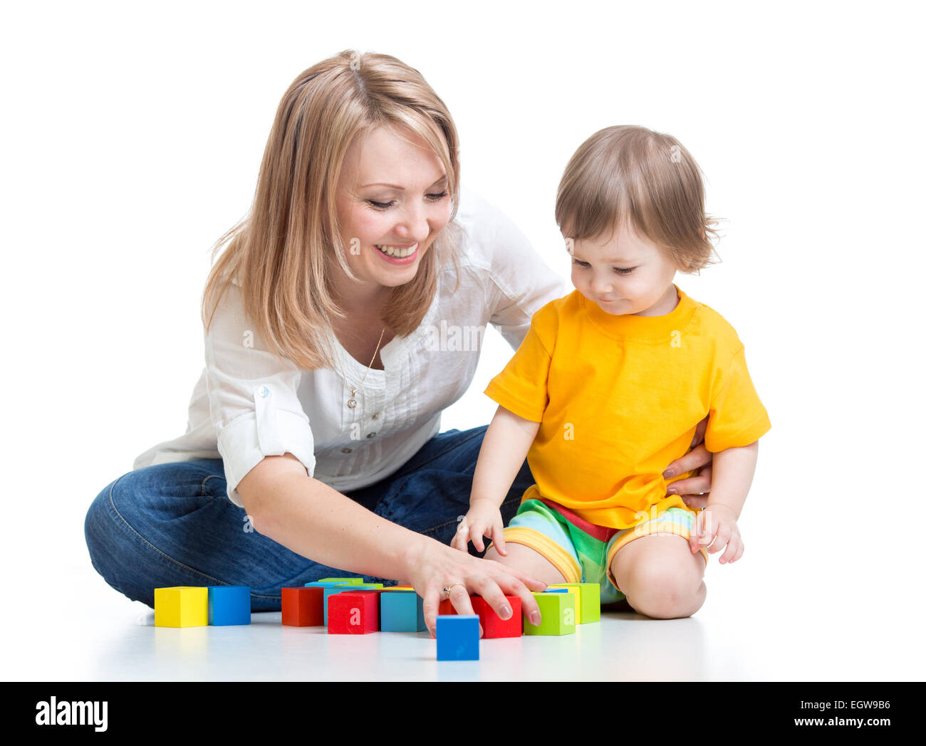 La madre y el bebé jugar con bloques de construcción toy aislado en blanco Foto de stock
