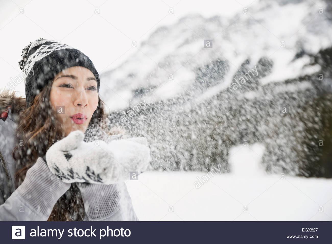 Mujer soplado de nieve por debajo de las montañas Imagen De Stock