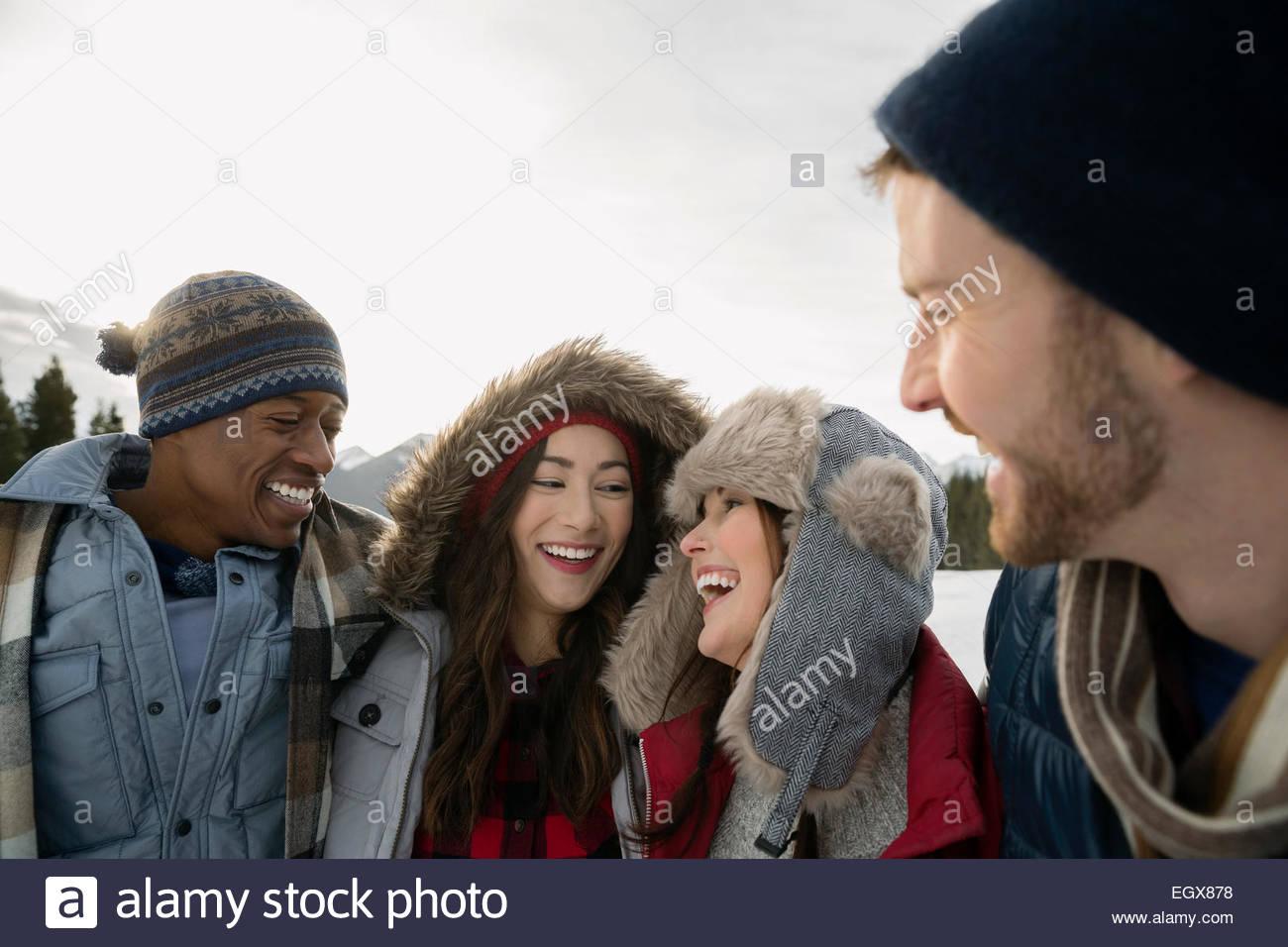 Las parejas en ropa de abrigo riendo al aire libre Imagen De Stock