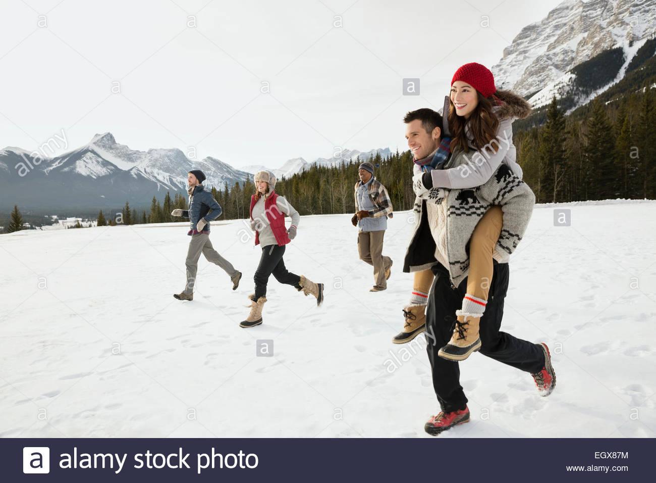 Amigos corriendo en campo nevado por debajo de las montañas Imagen De Stock