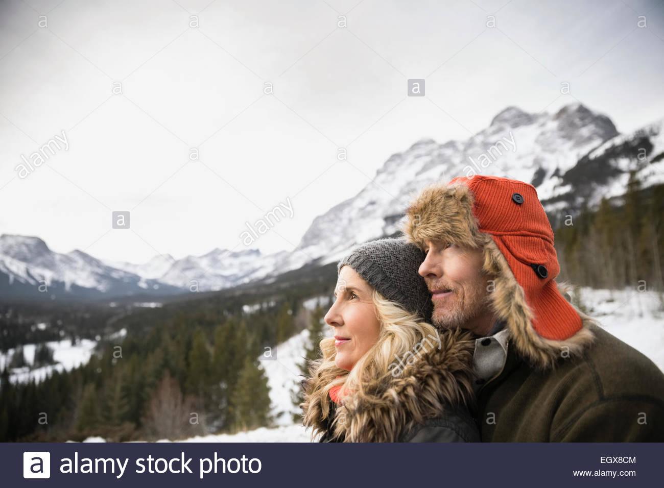 Pareja seria mirar lejos debajo de montañas nevadas Imagen De Stock