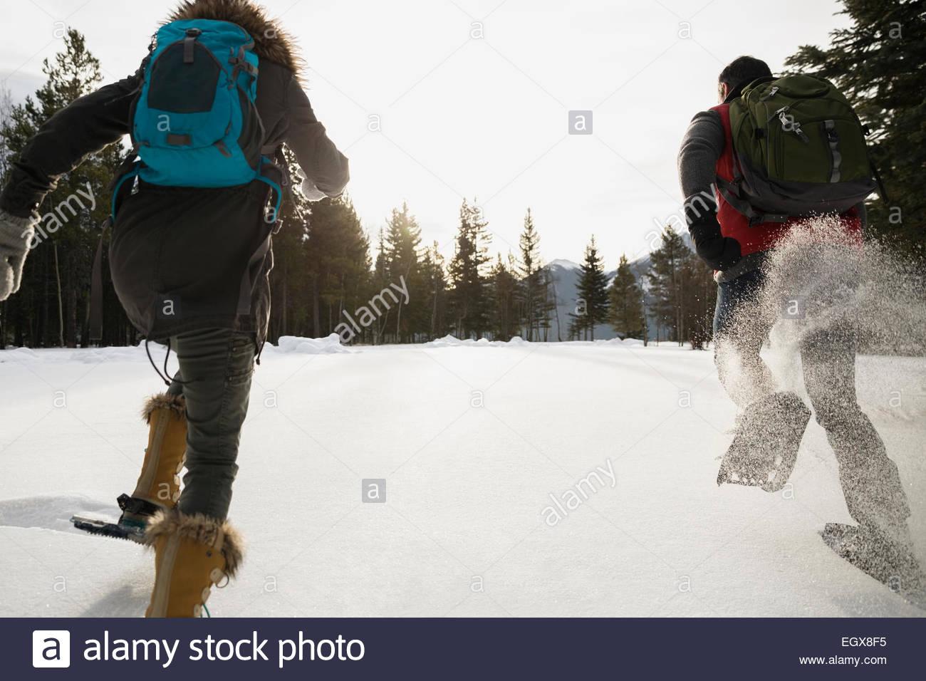 Amigos corriendo en raquetas de nieve en el campo nevado Imagen De Stock
