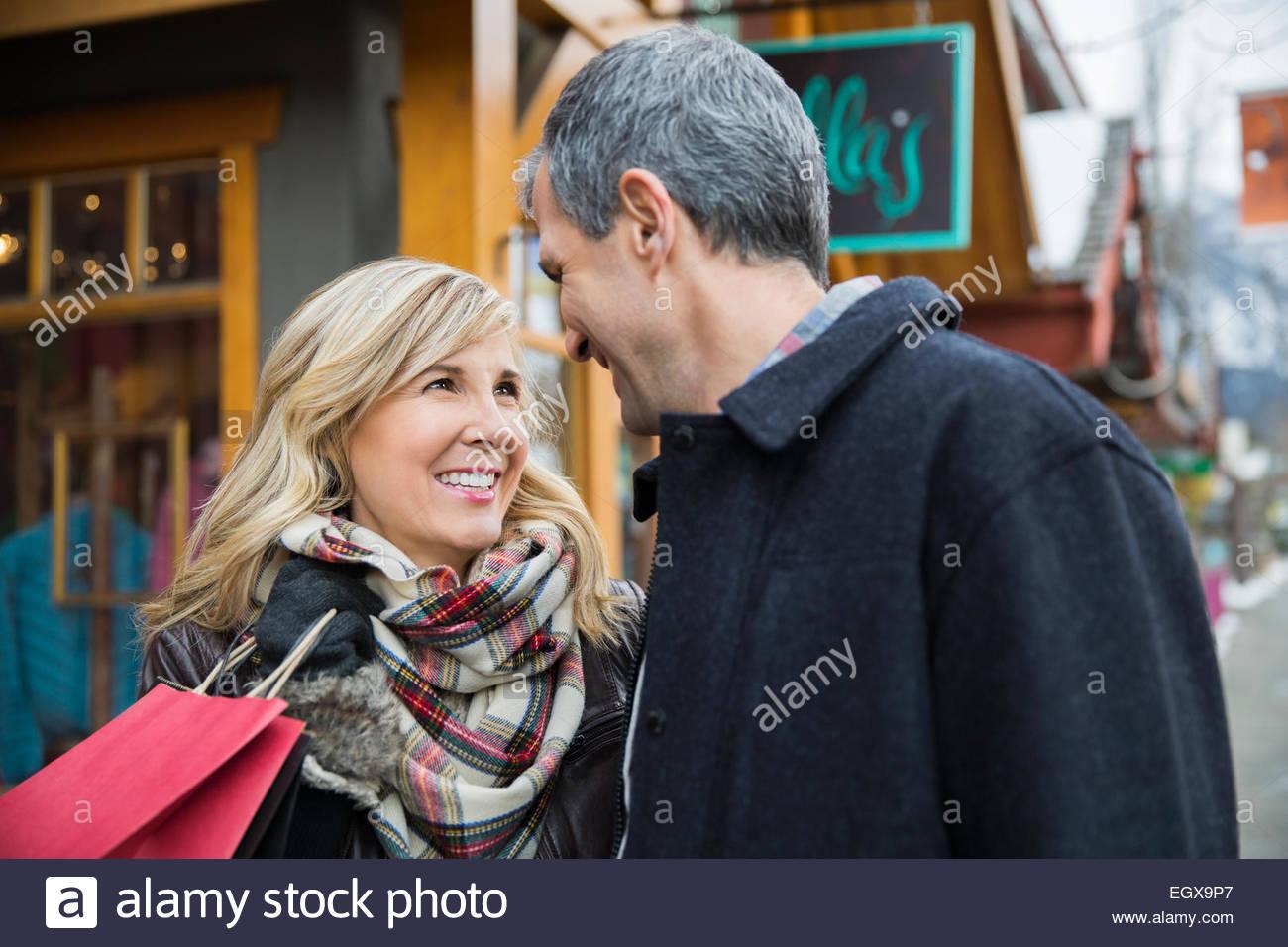Pareja sonriente con bolsa de compras fuera de escaparate Imagen De Stock