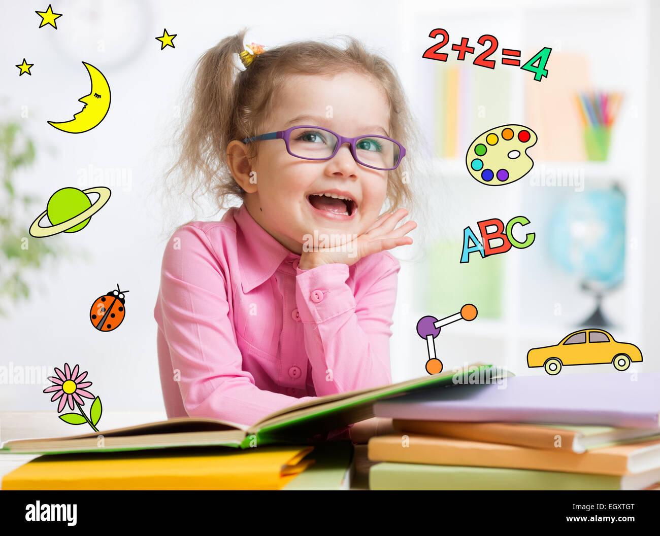Funny smart kid en las gafas de lectura en kindergarten. Imagen De Stock