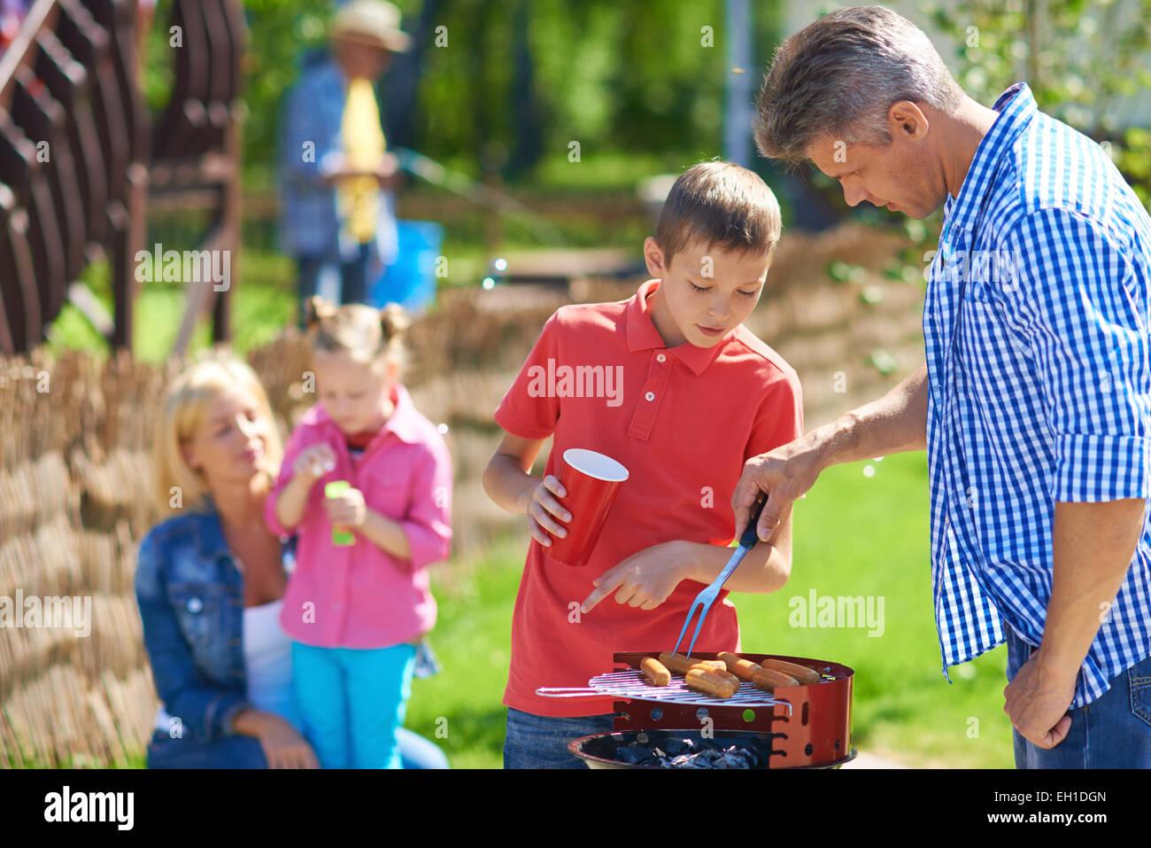 Padre e hijo freír las salchichas en su encuentro con la familia Imagen De Stock