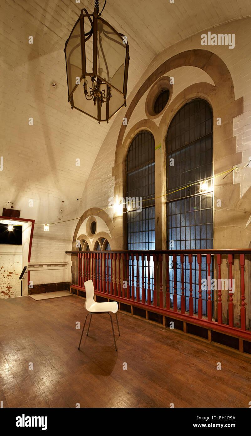 Silla de plástico en la parte frontal de grandes ventanas arqueadas, Capilla galesa, Londres, Reino Unido. Imagen De Stock