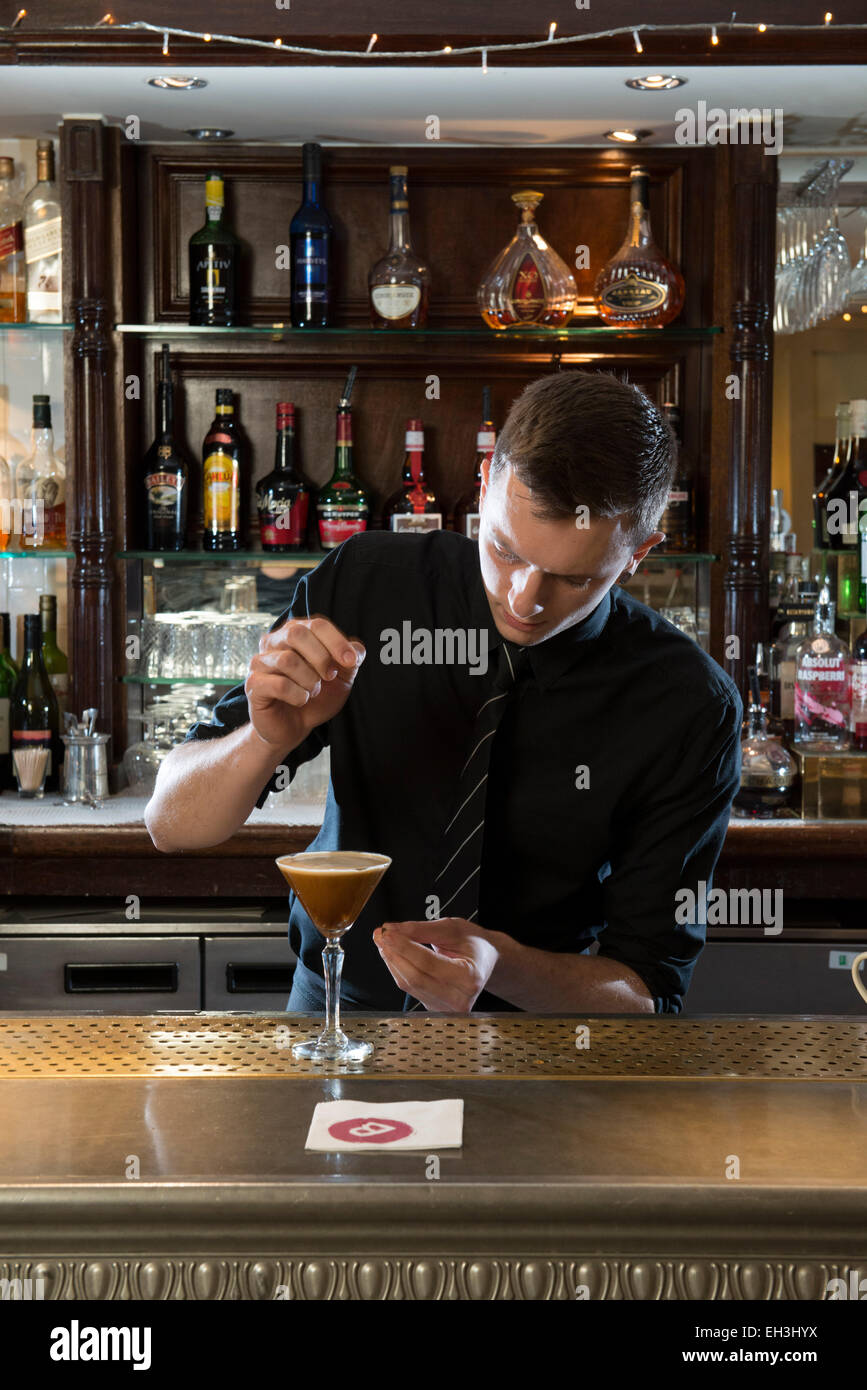 Un macho de barman, camarero, mixologist hace un fantástico cóctel en un restaurante / bar / public house Imagen De Stock