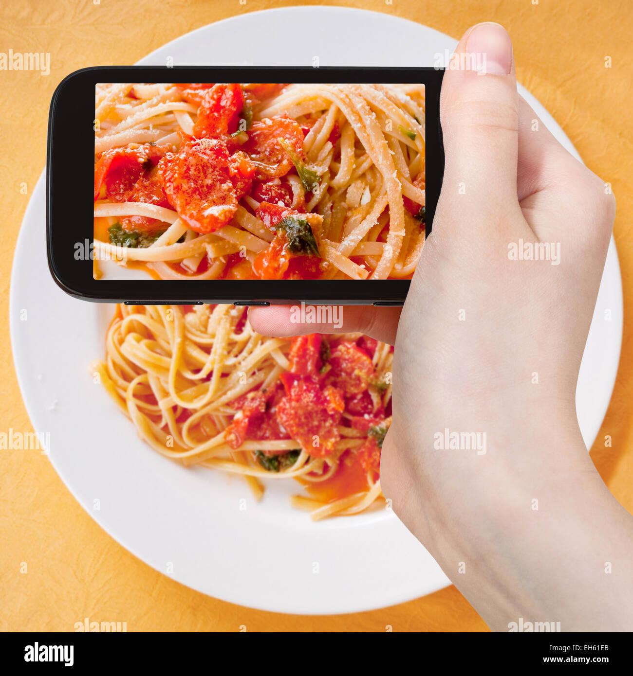 Fotografiar comida concepto - toma de fotografía turística de espaguetis con salsa de tomate picante sobre placa blanca en gadget móvil, Italia Foto de stock