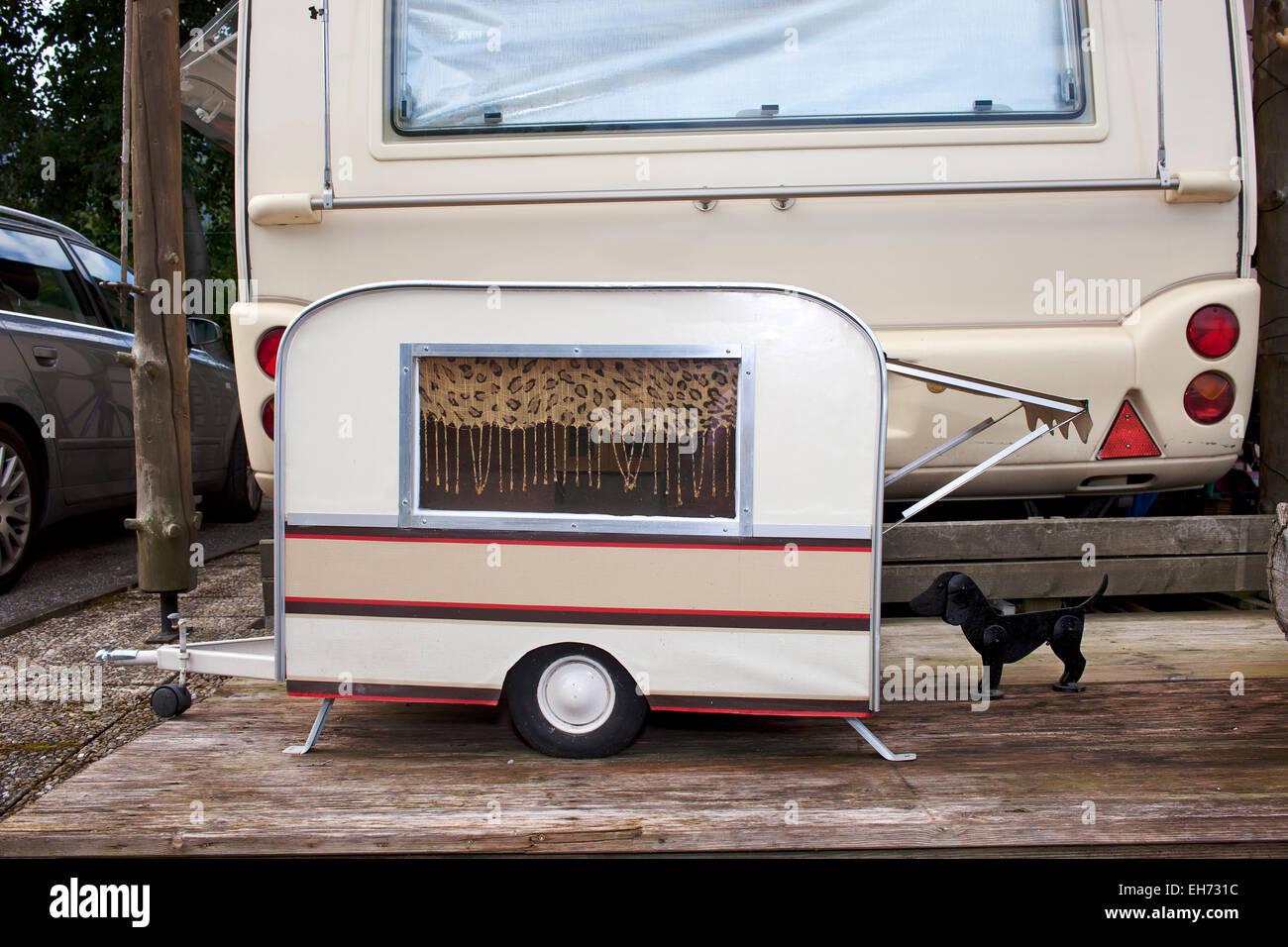 Modelo diminuto caravana por un pequeño perro mascota estacionado en la parte posterior de los propietarios a tamaño Foto de stock