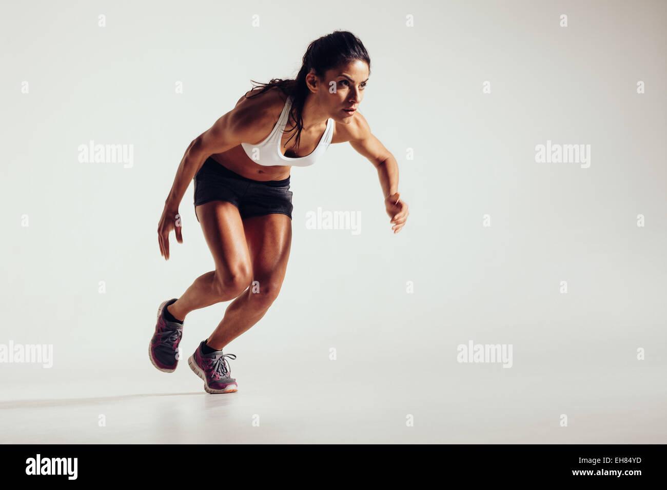 Joven comienza a correr y acelera con fondo gris. Potente joven atleta femenina girando en la competencia. Imagen De Stock