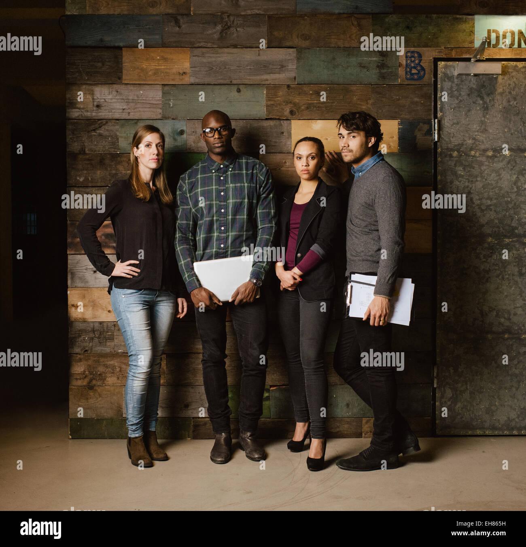 Imagen de longitud completa del equipo creativo multirracial posando para la cámara en la oficina. Jóvenes empresarios juntos contra un wo Foto de stock