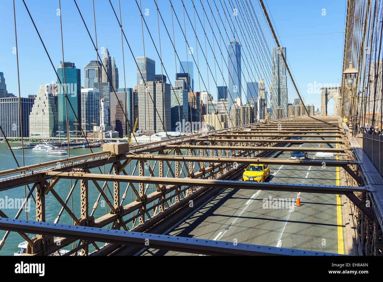 Taxi amarillo cruzando el Puente de Brooklyn con el horizonte de Manhattan Inferior, detrás de la ciudad de Imagen De Stock