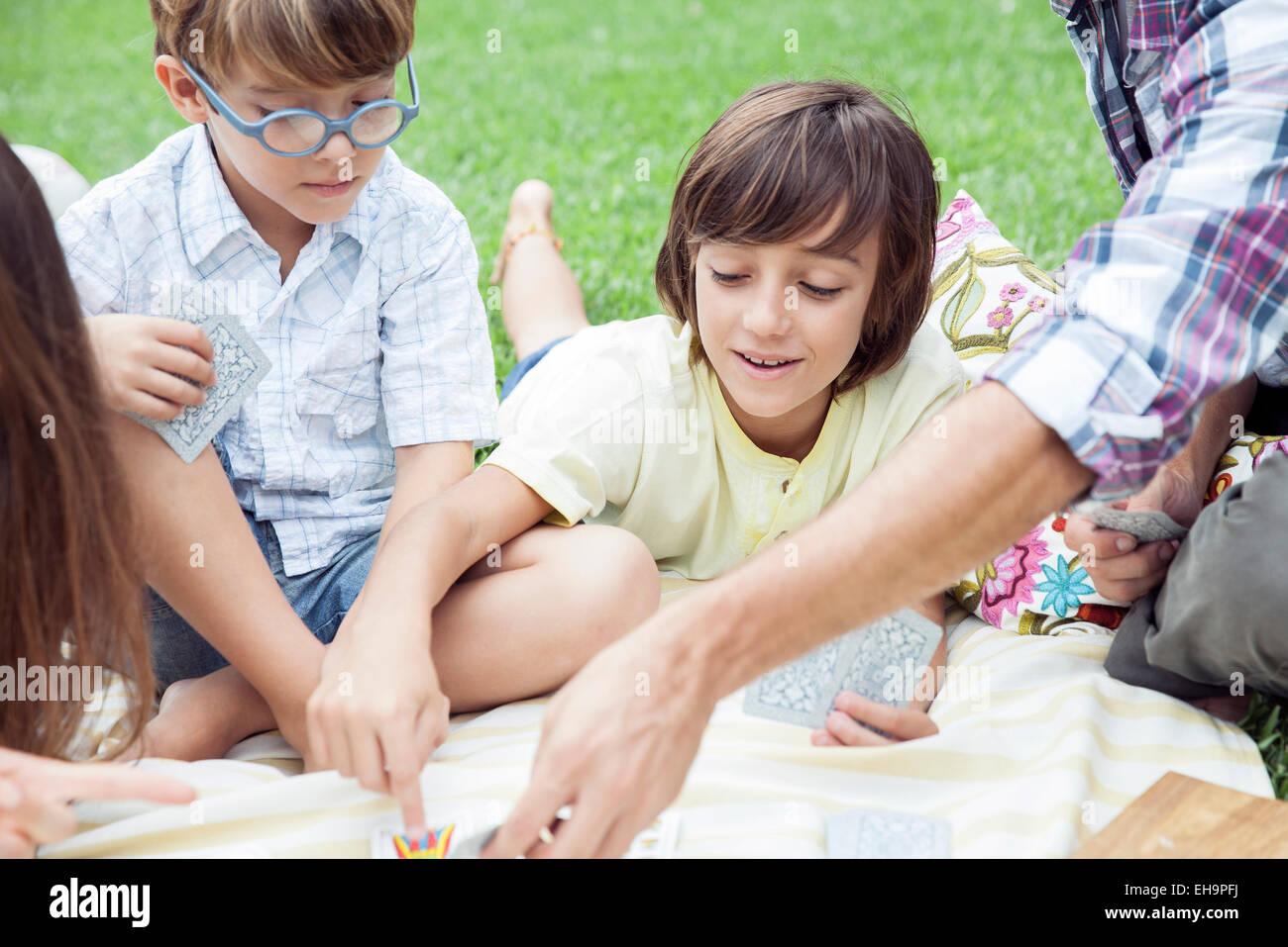 Muchachos jugando cartas a picnic familiar Imagen De Stock