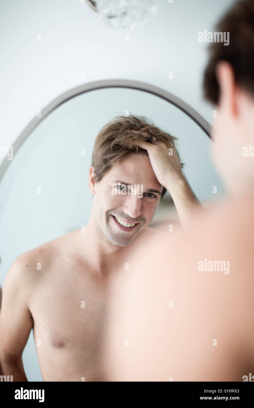 El hombre con las manos en el cabello en sí mismo en el espejo con apariencia de diversión Imagen De Stock