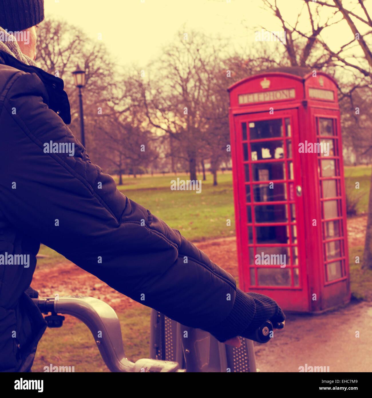 Un joven en bicicleta en invierno en Hyde Park en Londres, Reino Unido, con una típica cabina de teléfono Imagen De Stock