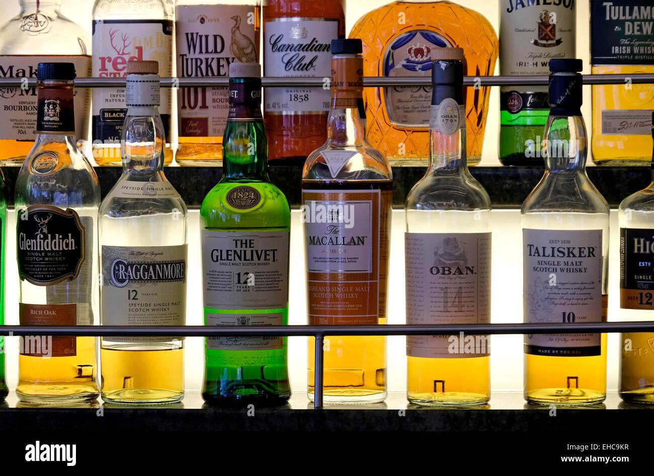 Selección de whiskys y otras bebidas licores en una estantería de cristal iluminado Imagen De Stock