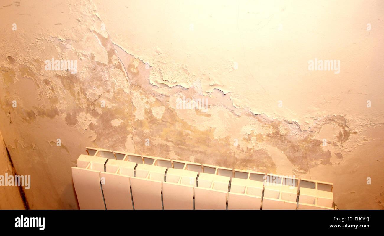 Humedad en una pared con un problema de agua del radiador de calefacción Foto de stock