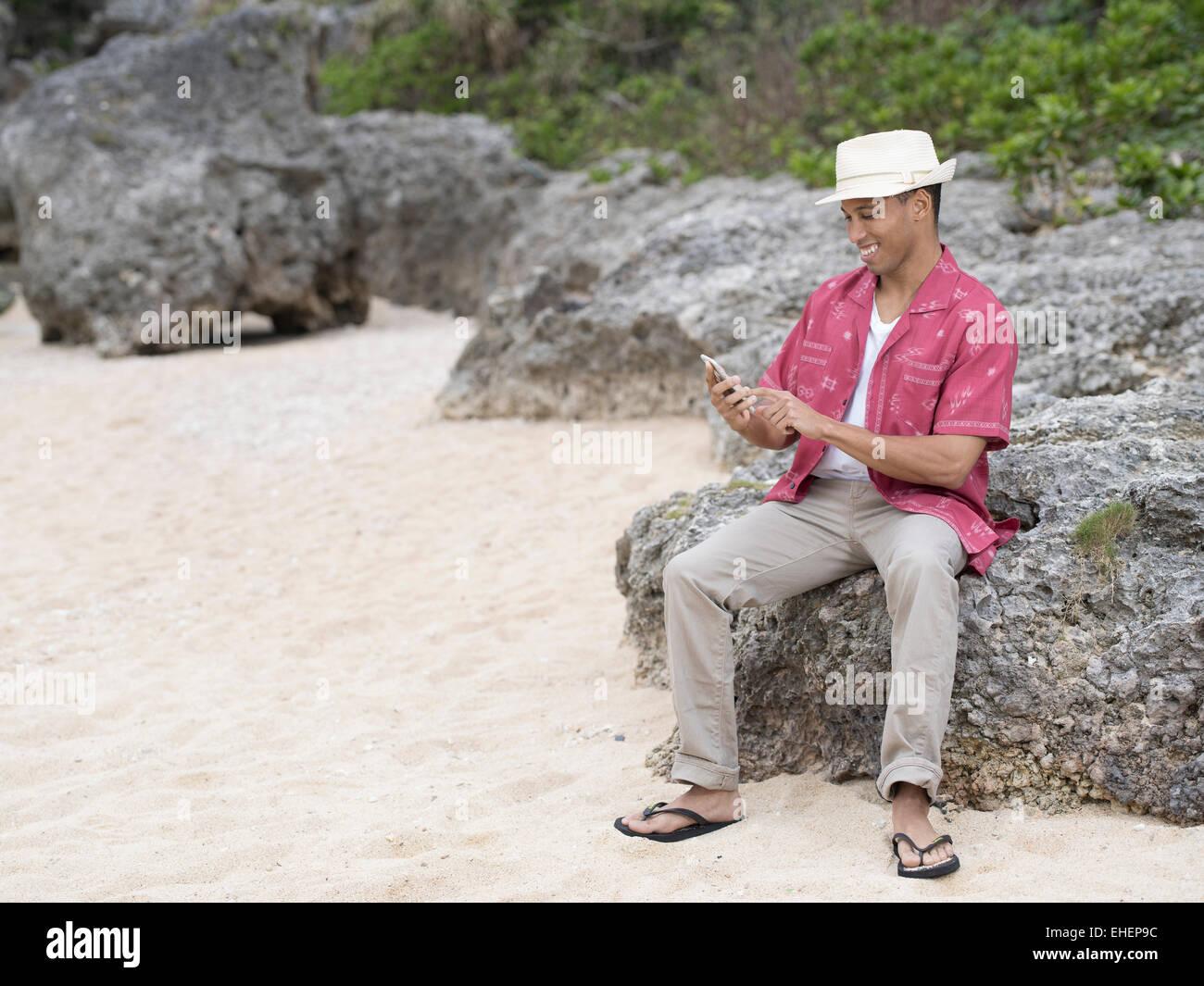 Hombre texting / control de internet en Apple iphone 6 smartphone mientras en la playa. Imagen De Stock