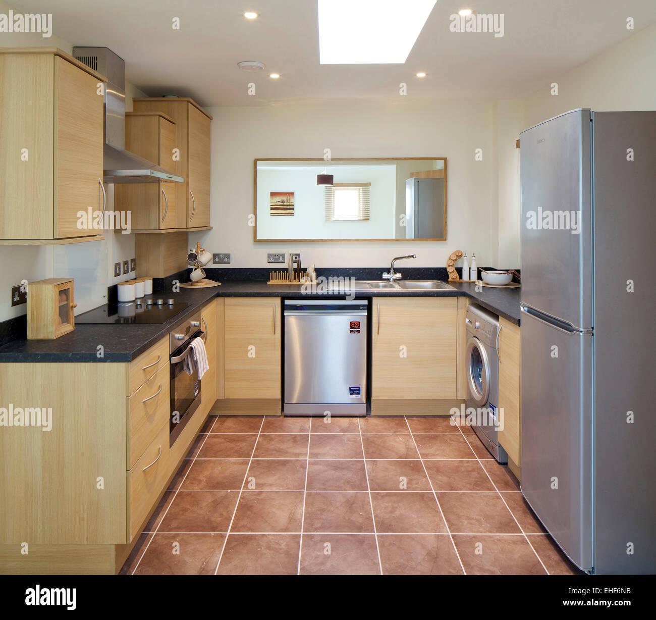 Cocina moderna con unidades de madera y piso de baldosas en el apartamento  al Lawley Village 5de5d4fc1b62