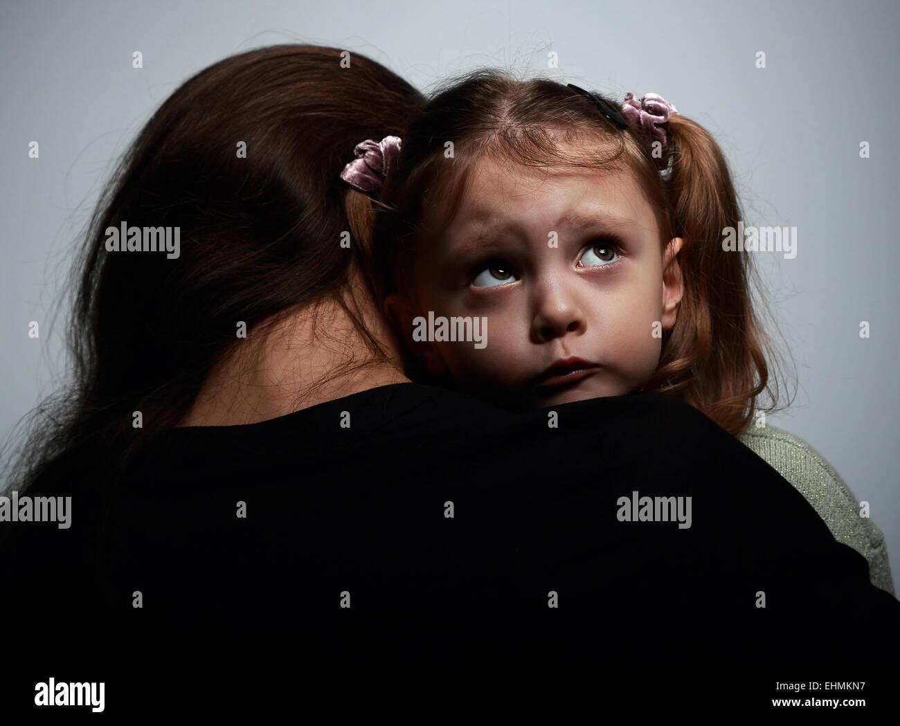 Pensamiento triste hija abrazando a su madre y mirando hacia arriba sobre fondo oscuro Imagen De Stock