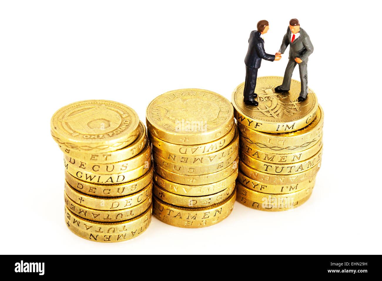 Dinero tratar presupuesto empresarial UK pound coins apila empresarios recortar recorte aislado fondo blanco. Imagen De Stock