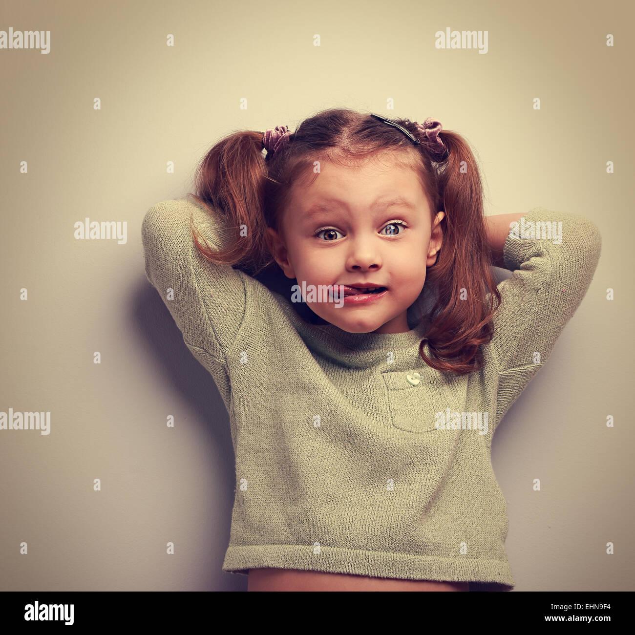 Funny Girl mostrando la lanza y lo sorprendente cara divertida. Retrato Vintage Imagen De Stock