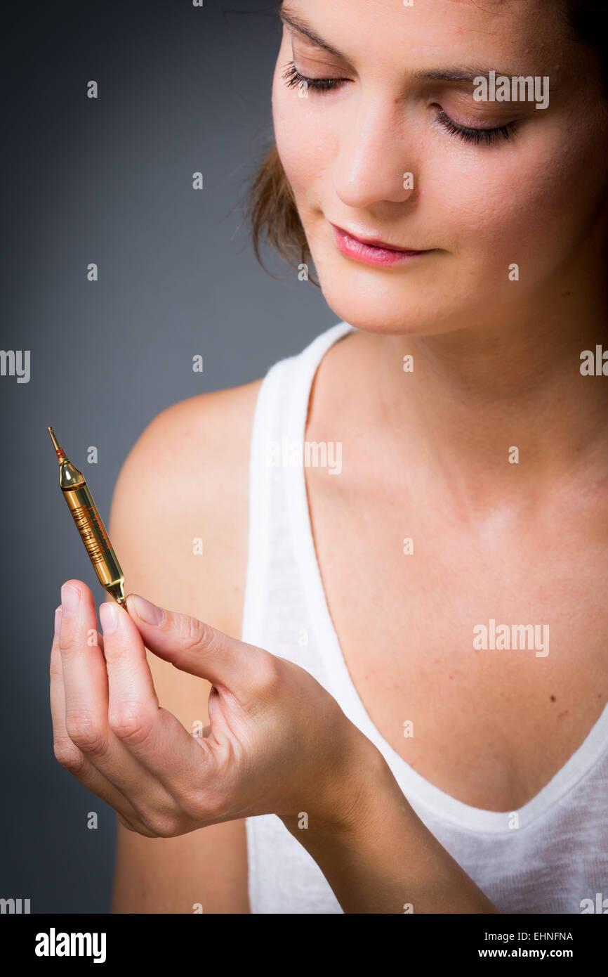 Mujer sosteniendo ampolla de vidrio de vitamina D. Foto de stock