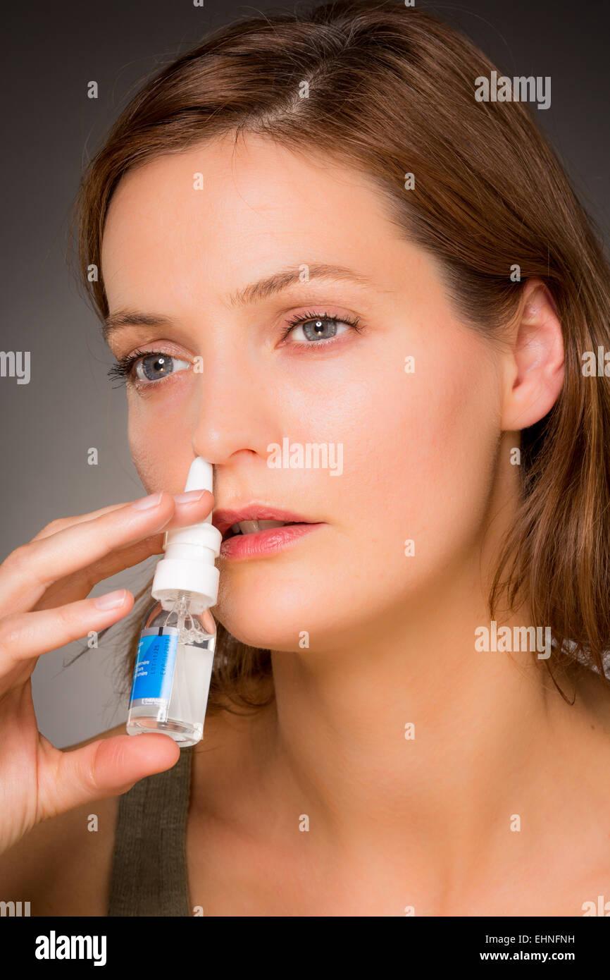 Mujer con aerosol nasal para controlar la rinitis. Imagen De Stock